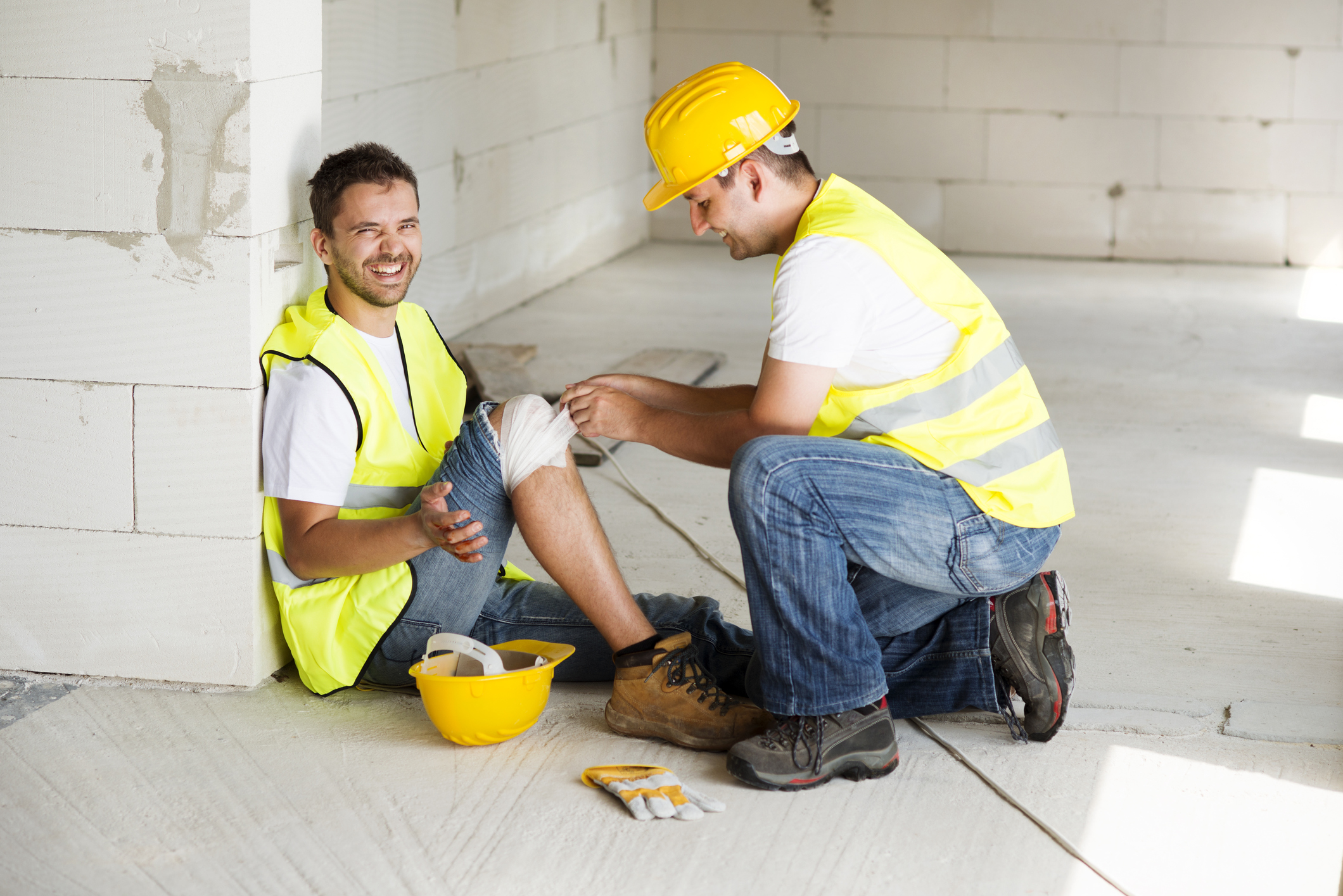 Man workplace physical injury with colleague helping to manage his knee